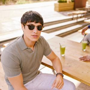 Sharply dressed man in sunglasses and a Moss Bros khaki polo