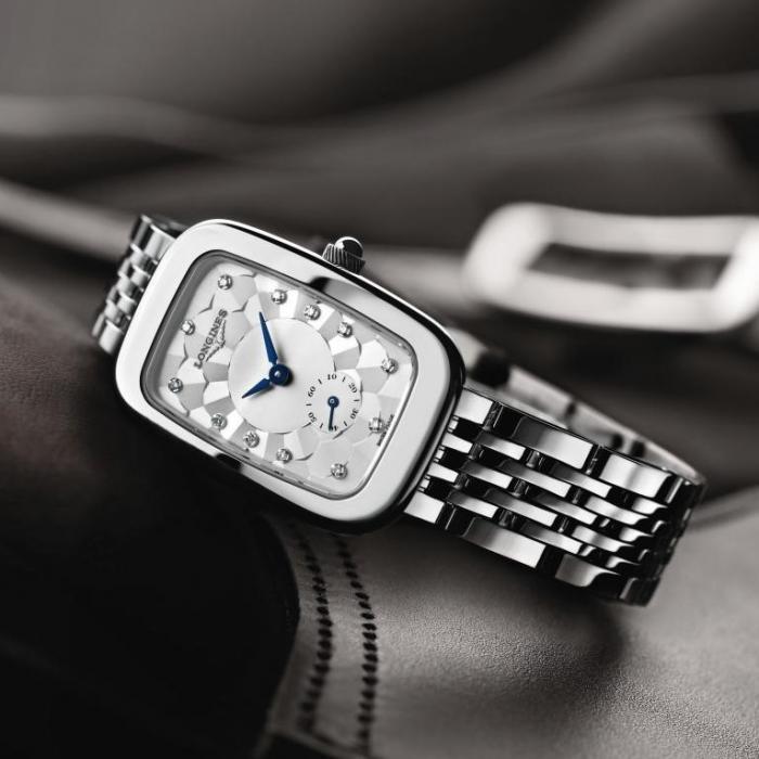 Luxury silver watch lying on a black leather satchel