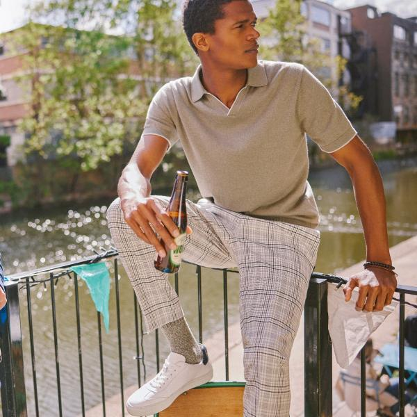 Model on a sunny balcony is holding a bottle of bear, wearing checked chinos and a smart grey top from Moss Bros