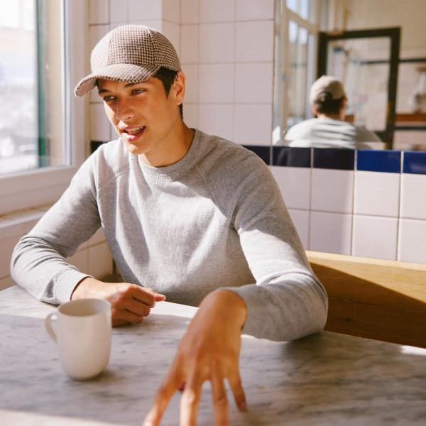 Model is sat in a sunny window booth at a cafe, wearing a cap and smart grey jumper from Moss Bros